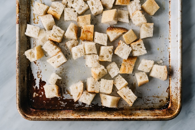 From above, cubes of sourdough on a baking sheet tossed with olive oil and salt for making croutons.