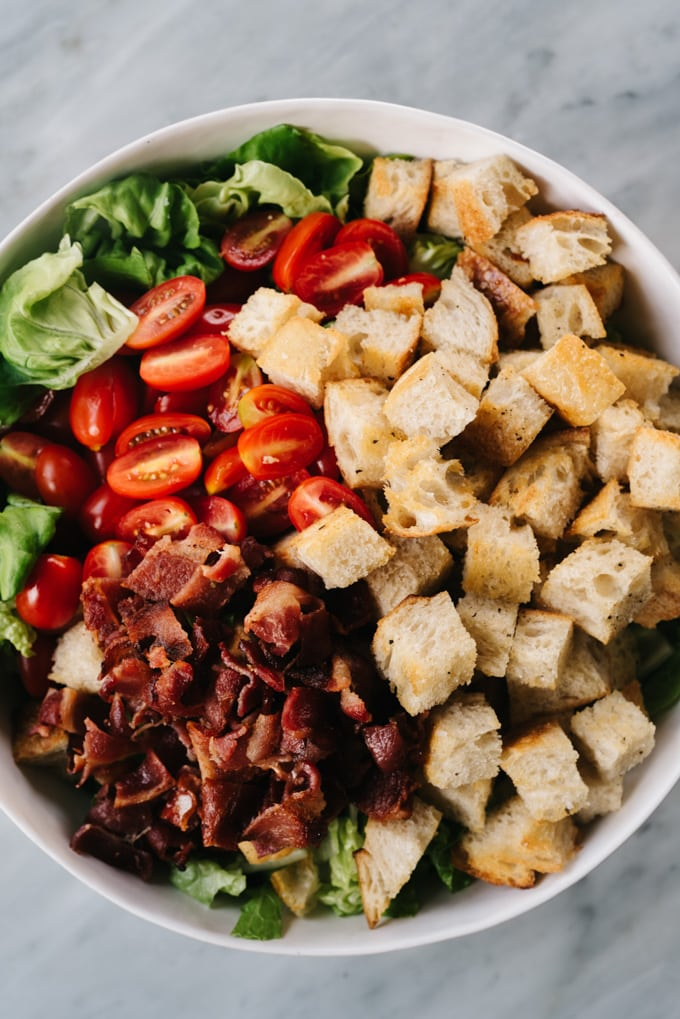 From above, a white salad bowl filled with the ingredients for a BLT salad - chopped lettuce, grape tomatoes, bacon, and sourdough croutons.