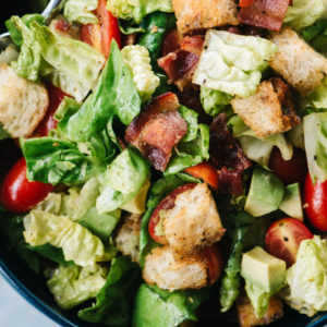 From above, a close-up of a BLT salad with avocado and hot bacon dressing.