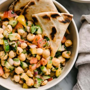A bowl of vegan mediterranean chickpea salad with cucumber, tomato, bell pepper, mint, parsley, and lemon.