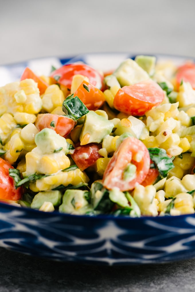 Side view detail of grilled tomato corn salad with avocado, basil, and creamy buttermilk dressing.
