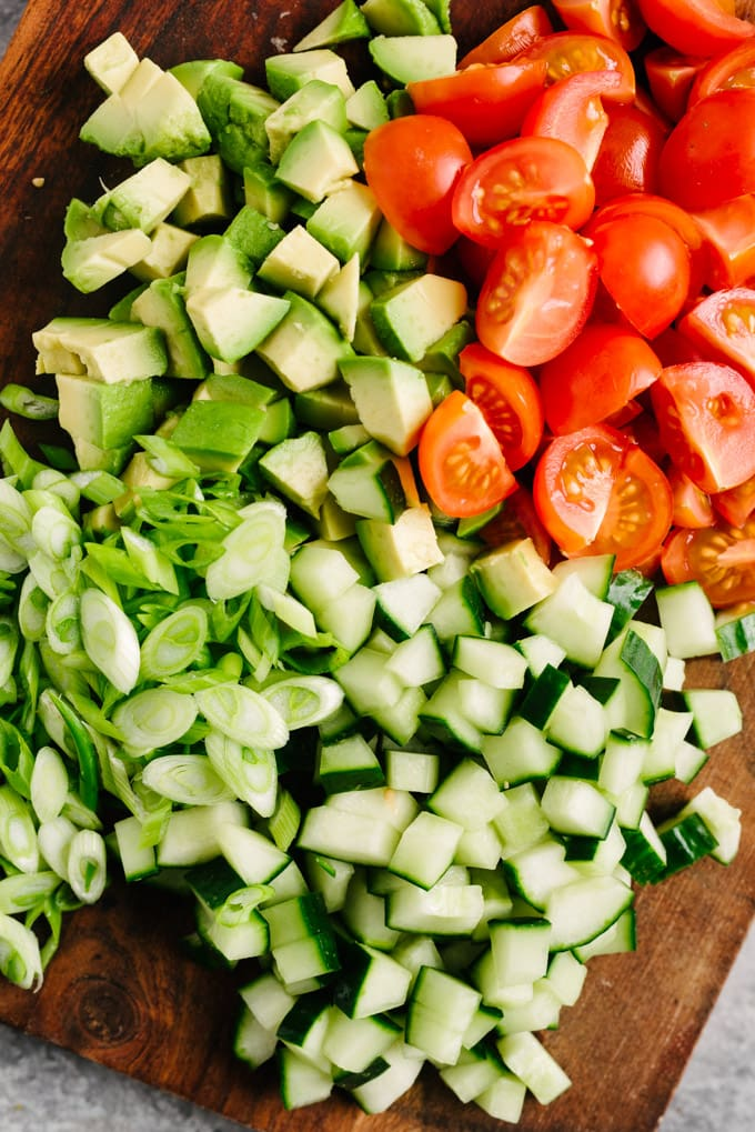 Overhead view of diced avocado, cucumber, tomatoes, and sliced green onions on a cutting board.