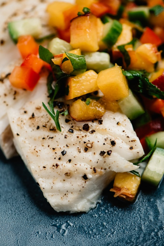 Side view, oven baked halibut fillet topped with fresh peach salsa.