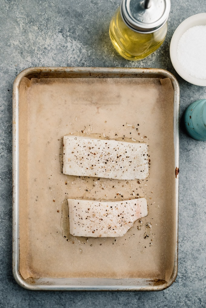 Two halibut fillets on a parchment lined baking sheet seasoned with olive oil, salt, and pepper.