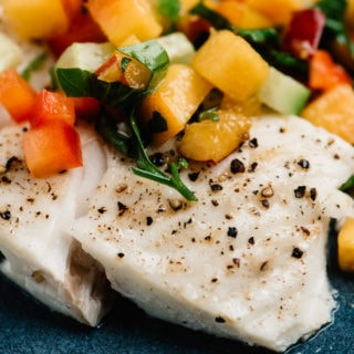 Side view, baked halibut fillet topped with fresh peach salsa.