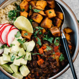 From above, black bean bowl with quinoa, roasted sweet potatoes, citrus black beans, avocado, radish, and cilantro.