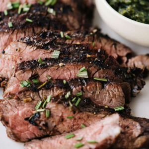 Thin slices of rosemary steak on a white plate with a small bowl of pesto on the side.
