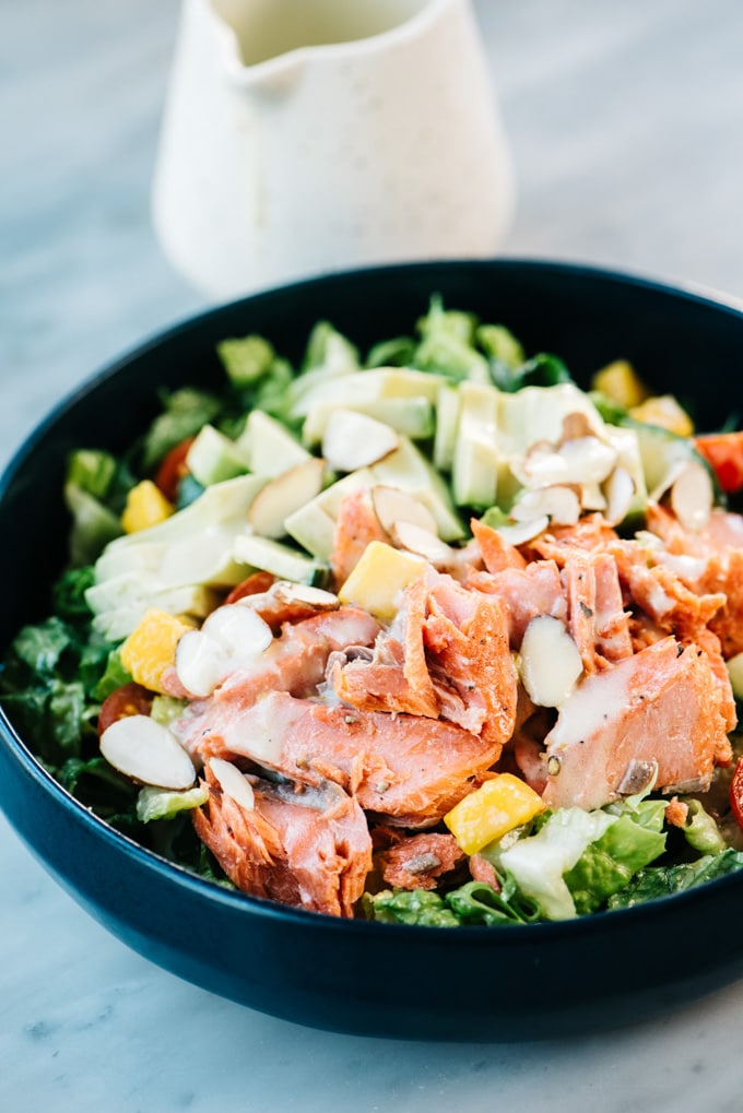 Side view, salmon and avocado salad in a blue bowl with a small pitcher of lemon dressing on the side.