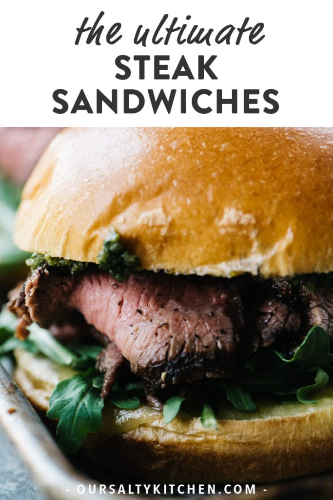 A grilled steak sandwich with sharp cheddar, arugula, thinly sliced steak, and pesto on a brioche bun.