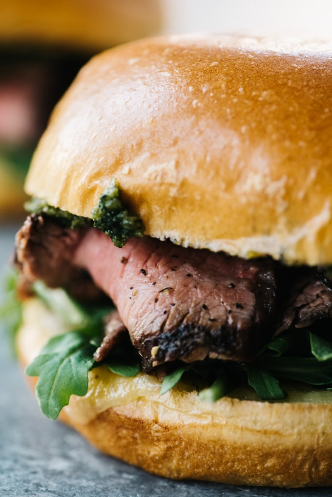 A close-up view of a grilled steak sandwich with sharp cheddar, arugula, thinly sliced steak, and pesto on a brioche bun.