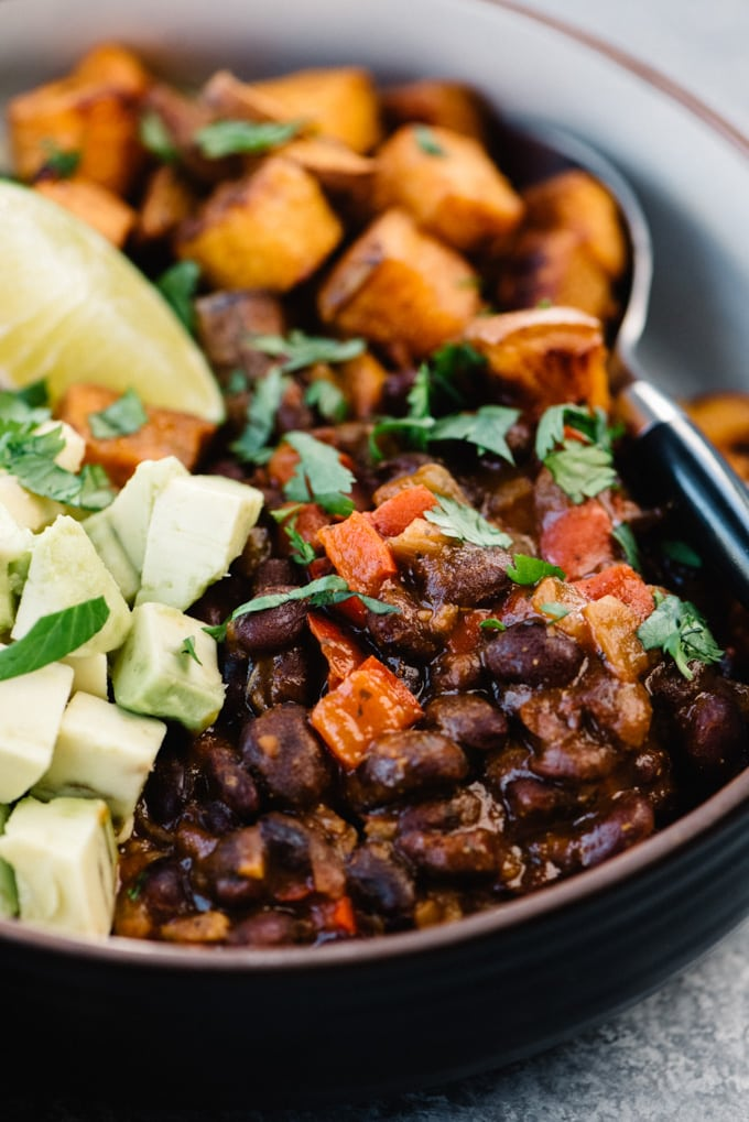 Side view, close up of citrus black beans in a vegan black bean buddha bowl.