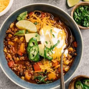 A bowl of weeknight ground beef taco soup surrounded by garnishes on a cement background.