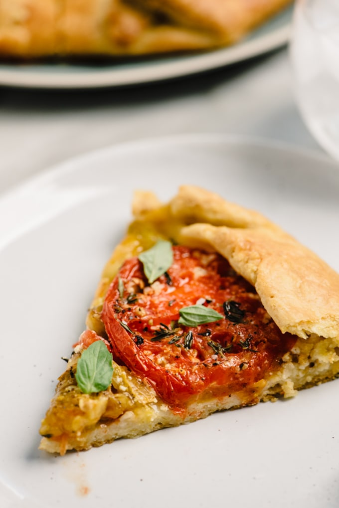 A slice of heirloom tomato galette on a white plate.
