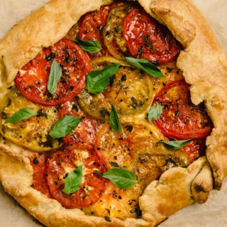From above, baked heirloom tomato galette sprinkled with fresh basil.