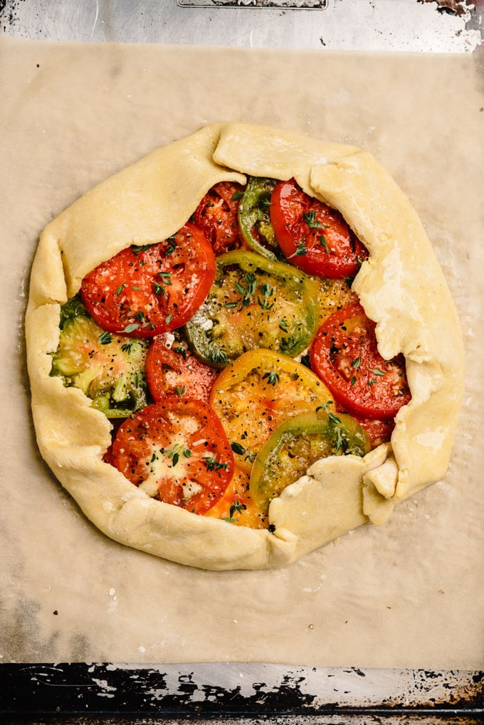 A prepared tomato galette on a baking sheet before being transferred to the oven.