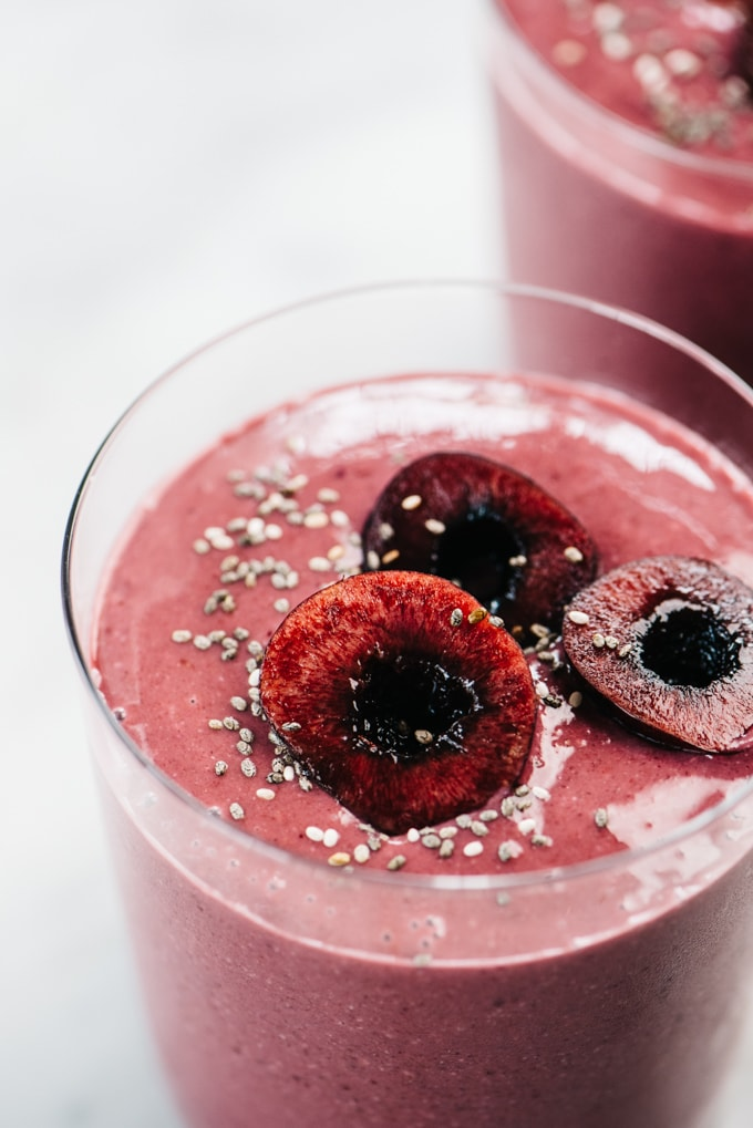 Side view, a close-up of a cherry smoothie in a glass garnished with fresh cherries and chia seeds.