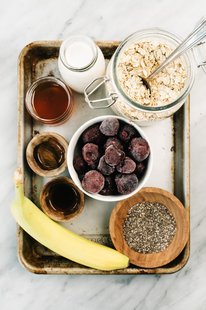From above, the ingredients for a vegan cherry pie smoothie arranged on a baking sheet.