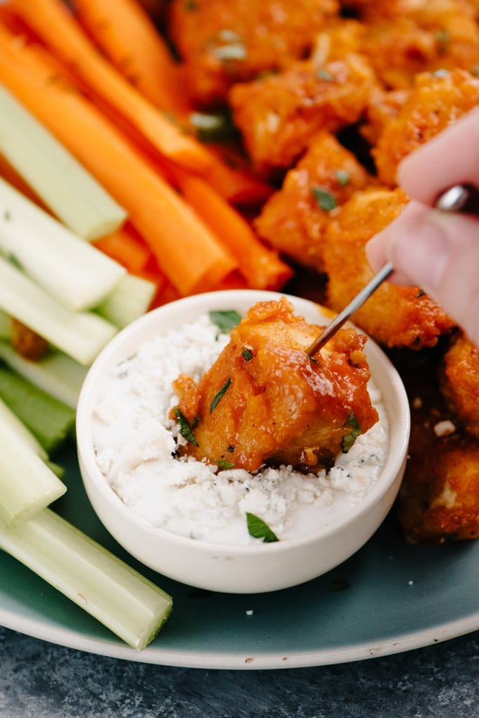 A buffalo chicken bite on a cocktail stick being dipped into blue cheese dressing.