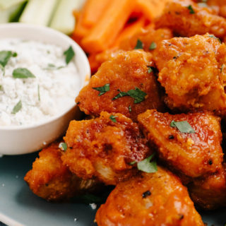 Side view of buffalo chicken bites appetizer on a blue plate with celery and carrot sticks and blue cheese dressing.