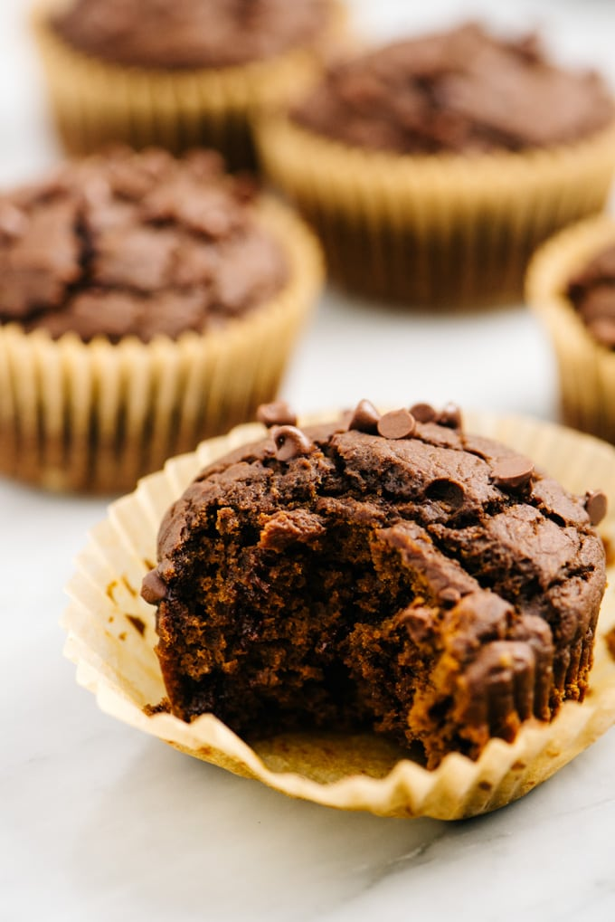 A chocolate pumpkin muffin with a bite missing showing the moist interior.