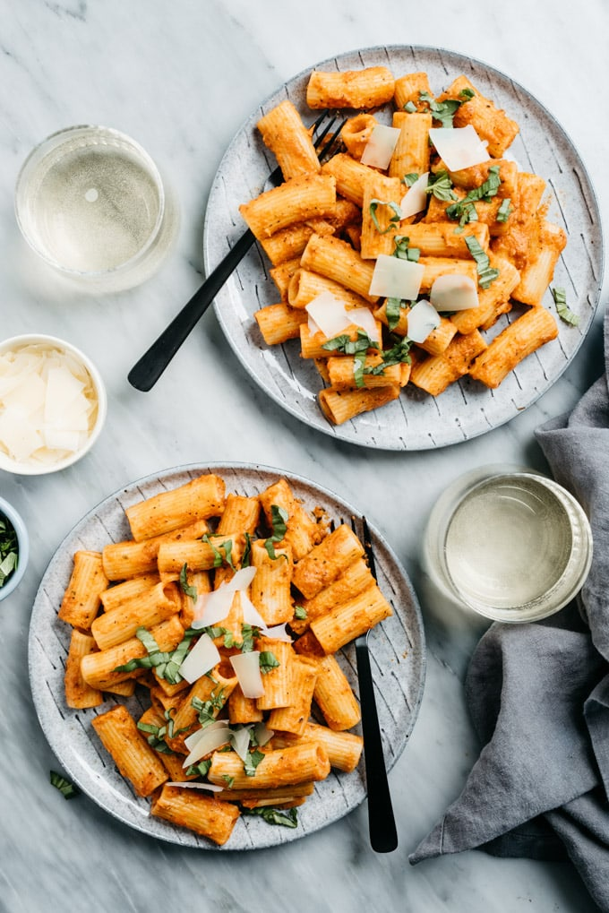 Two plates of rigatoni tossed in creamy tomato sauce on a marble table with white wine and a small bowl of parmesan cheese.