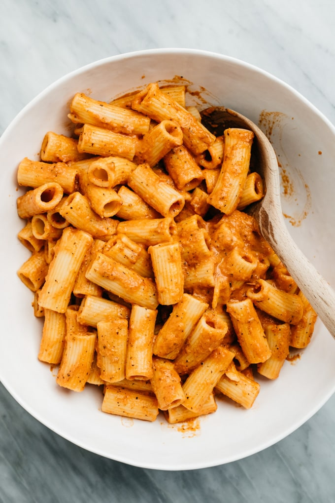 Cooked rigatoni pasta tossed with tomato cream sauce in a large white bowl.