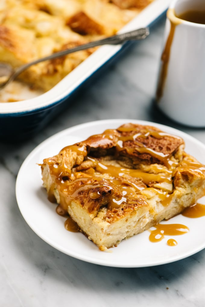 A slice of apple bread pudding drizzled with salted caramel sauce.