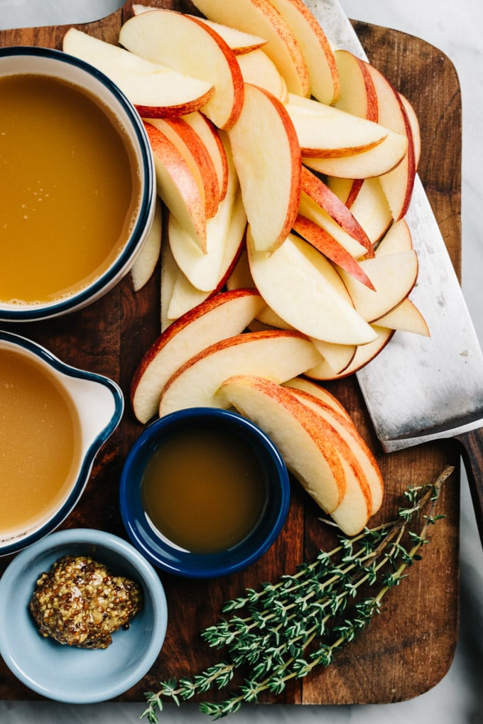 Ingredients for apple chicken with cider sauce on a cutting board.