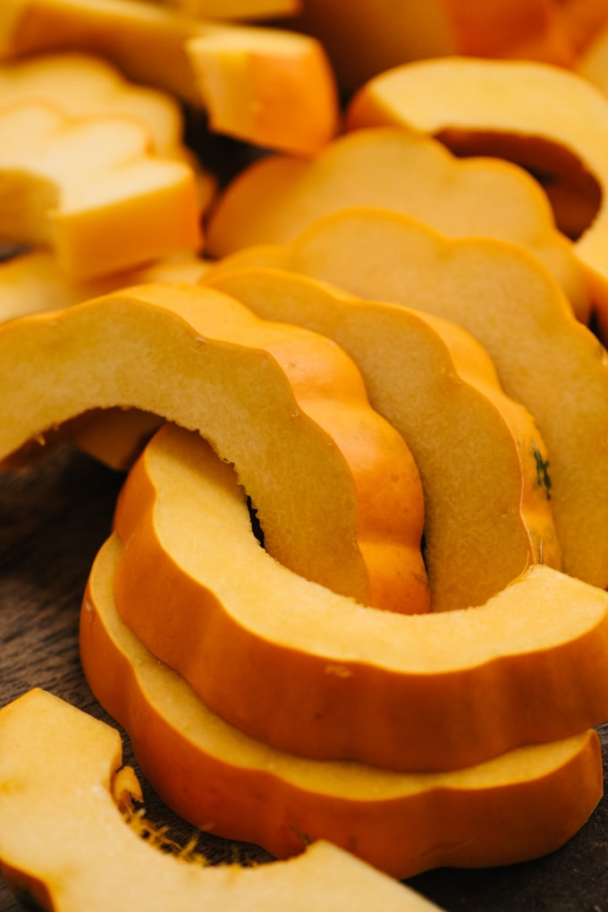 Acorn squash slices on a cutting board.
