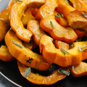 A platter of roasted acorn squash with maple brown butter garnished with fresh sage.