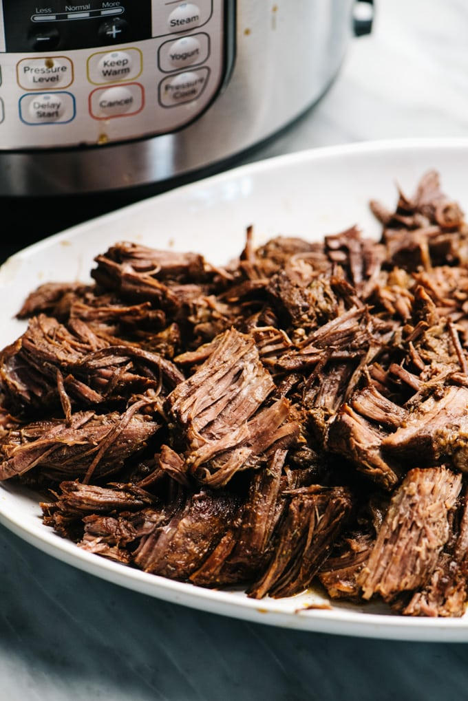Shredded pot roast cooked in the instant pot on a white platter.