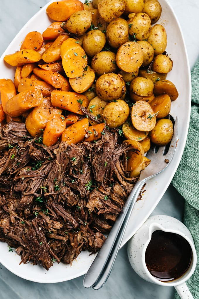 A platter of instant pot pot roast with carrots, potatoes, and gravy.